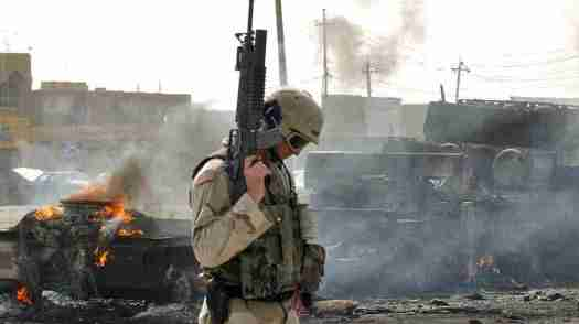 A U.S. Army soldier guards the remains of a burned-out military ammunition truck after it was attacked in Fallujah, Iraq, on Oct. 19, 2003. Fallujah and its surrounds were the site of some of the bloodiest fighting for U.S. troops during the Iraq war. Khalid Mohammed/AP