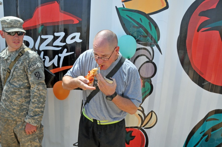 Sgt. William Paulk of the 900th Maintenance Company, Alabama National Guard, eats his first slice of Pizza Hut pepperoni pizza at the grand opening of the facility at Forward Operating Base Deh Dadi II. The Pizza Hut completes the food court on the FOB, as the 530th Combat Sustainment Support Battalion continues to expand construction projects there.