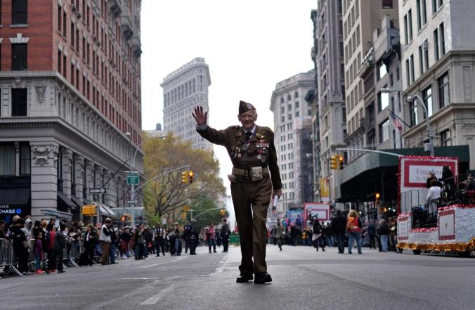 A US war veteran waves as he takes part in a Veterans Day Parade in New York. (Jewel Samad/AFP/Getty Images)
